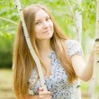 Portrait of a beautiful young woman with brown long hair on nature in a dress with a floral pattern. Girl resting in a birch forest — Stock Photo #52160247