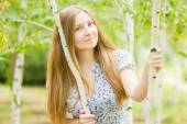 Portrait of a beautiful young woman with brown long hair on nature in a dress with a floral pattern. Girl resting in a birch forest — Stock Photo
