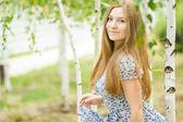 Portrait d'une belle jeune femme avec des cheveux longs brun sur la nature dans une robe avec un motif floral. fille au repos dans une forêt de bouleaux — Photo