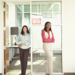 Businesswomen smiling for the camera in office space — Stock Photo #52026611