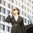 Asian businesswoman using cell phone next to car — Stock Photo #52026963