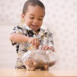 Young boy putting money in piggy bank — Stock Photo #52027121