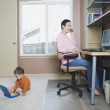Pregnant woman working at home with young son — Stock Photo #52027379