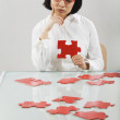 Asian woman putting together puzzle — Stock Photo #52027759