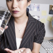 Asian businesswoman taking medication at desk — Stock Photo #52028013