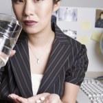 Asian businesswoman taking medication at desk — Stock Photo #52028013