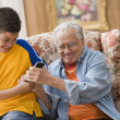 Young boy and his grandfather fighting over the remote control — Stock Photo #52028149
