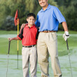 Hispanic father and son on hugging on golf course — Stock Photo #52028381