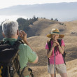 Senior man taking a picture of his wife on a hike — Stock Photo #52028775