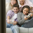 Four teenagers on couch playing video games — Stock Photo #52029215