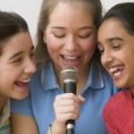 Three girls singing with microphone — Stock Photo #52029353