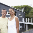 Multi-ethnic couple holding champagne in front of house — Stock Photo #52029363