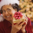 Senior Hispanic woman holding Christmas gift — Stock Photo #52029597