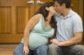Pregnant couple kissing outdoors — Stock Photo