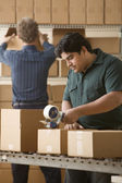 Young man taping a cardboard box closed — Stock Photo