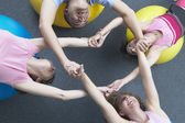 Exercise group grabbing hands — Stock Photo
