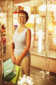 Hispanic woman with shopping bags looking in shop window — Stock Photo