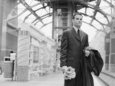 Man holding flowers and waiting at train station — Stock Photo