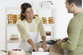 Woman at bakery helping customer — Stock Photo