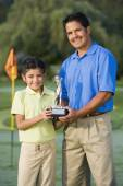 Hispanic father and daughter holding golf trophy — Stock Photo
