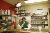 Pharmacist sitting behind counter — Stock Photo