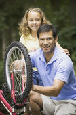 Hispanic father fixing daughter's bicycle — Stock Photo