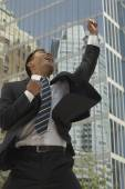 Asian businessman cheering in front of sky scraper — Stock Photo
