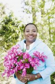 African woman holding bouquet of flowers outdoors — Stock Photo