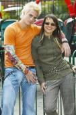 Teenage Hispanic punk couple hugging at carnival — Stock Photo