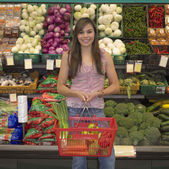 Young woman in produce section of supermarket — Stock Photo