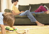 Parents on sofa and young son playing with trains on floor — Stock Photo