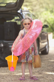 Young girl in flip flops with beach toys — Stock Photo