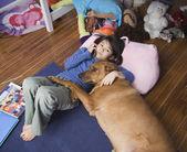 Asian girl with dog on floor — Stock Photo