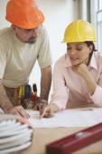 Construction workers reading blue prints — ストック写真