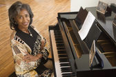 Senior African woman sitting at piano — Stock Photo