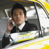 Businessman talking on cell phone in cab — Stock Photo