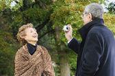 Senior man talking senior woman's photograph outdoors — Stock Photo