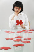 Asian woman putting together puzzle — Stock Photo