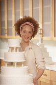 African female baker next to a wedding cake — Stock Photo