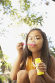 Hispanic girl blowing bubbles outdoors — Stock Photo