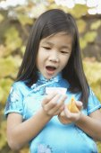 Young Asian girl holding a fortune cookie and reading her fortune — Stock Photo