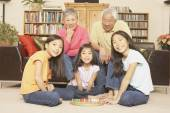 Asian sisters playing chinese checkers while grandparents watch — Stock Photo