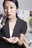 Asian businesswoman taking medication at desk — Stock Photo