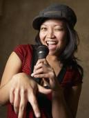 Asian woman singing with microphone — ストック写真