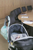 Baby in stroller next to conference table — Stock Photo