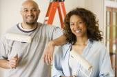 African couple holding paint rollers — Stock Photo
