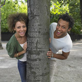 Couple peeking around opposite sides of tree — 图库照片