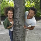 Couple peeking around opposite sides of tree — ストック写真