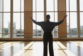 Businessman standing in sunlit room with arms outstretched — Стоковое фото