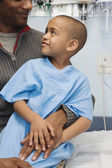 African boy in hospital gown sitting on father's lap — Foto Stock